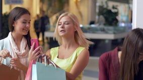 Οι φίλες Shopaholics παίρνουν selfie τη φωτογραφία στο smartphone με τις συσκευασίες αγορών μετά από τις αγορές στην ακριβή μόδα φιλμ μικρού μήκους
