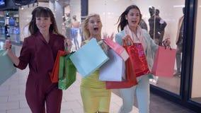 Οι φίλες Shopaholics πιέζουν χρονικά επάνω στις εποχιακές εκπτώσεις στη μπουτίκ μόδας κατά τη διάρκεια της μαύρης Παρασκευής στη  απόθεμα βίντεο
