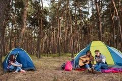 Οι φίλοι ακούνε μουσική κιθάρων Υπόλοιπο τουριστών στη φύση Στοκ Φωτογραφίες