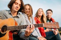 Οι φίλοι ακούνε busker ελεύθερος χρόνος τέχνης παιχνιδιού μουσικών στοκ εικόνες