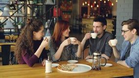 Οι φίλοι γιορτάζουν τη συγκέντρωση στον καφέ πέρα από τα ποτά και την πίτσα, clanging φλυτζάνια, πίνουν και μοιράζονται τις ειδήσ απόθεμα βίντεο