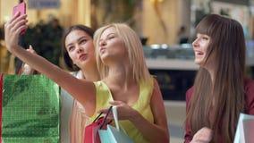 Οι φίλοι γυναικών Shopaholics φωτογραφίζονται σε ένα κινητό τηλέφωνο με τις τσάντες αγορών μετά από αγοράζουν μέσα τις ακριβές μπ απόθεμα βίντεο