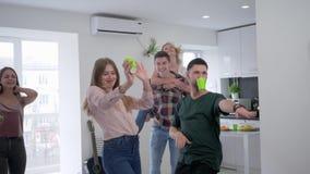 Οι φίλοι γύρω από στο σπίτι το κόμμα, η νεολαία χορεύει και έχει τη διασκέδαση στην κουζίνα με τα πλαστικά γυαλιά στο τους φιλμ μικρού μήκους