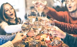 Οι φίλοι ομαδοποιούν το γιορτάζοντας κόμμα γευμάτων κρασιού σαμπάνιας Χριστουγέννων ψήνοντας στο σπίτι στοκ φωτογραφία
