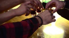 Οι φίλοι πίνουν τους οινοπνευματώδεις πυροβολισμούς στο νυχτερινό κέντρο διασκέδασης Τοπ άποψη των αρσενικών χεριών που παίρνουν  φιλμ μικρού μήκους
