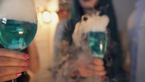 Οι φίλοι που κρατούν τα μπλε κοκτέιλ με τον άσπρο καπνό, κόμμα αποκριών, τέχνασμα ή μεταχειρίζονται απόθεμα βίντεο