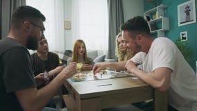 Οι φίλοι που παίζουν στο στρατηγικό επιτραπέζιο παιχνίδι με τις κάρτες και χωρίζουν σε τετράγωνα στο άνετο καθιστικό απόθεμα βίντεο