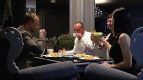 Οι φίλοι στηρίζονται για τα σούσια σε ένα εστιατόριο και πίνουν τα κοκτέιλ, καφές κίνηση αργή απόθεμα βίντεο