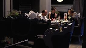 Οι φίλοι στηρίζονται στον καναπέ στο εστιατόριο τρώνε τα σούσια και πίνουν τον καφέ, πυροβολισμός ολισθαινόντων ρυθμιστών κίνηση  απόθεμα βίντεο