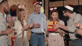 Οι φίλοι συγχαίρουν τη γυναίκα σε μια γιορτή Χριστουγέννων, ανοίγει το δώρο απόθεμα βίντεο