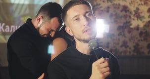 Οι φίλοι τραγουδούν τα τραγούδια καραόκε περνώντας καλά μαζί σε έναν φραγμό απόθεμα βίντεο