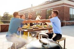 Οι φίλοι ψήνουν τα ποτά στο κόμμα σχαρών στη στέγη στοκ εικόνα