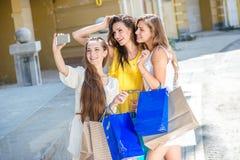 Οι φίλες κάνουν selfie σε ένα τηλέφωνο κυττάρων Κορίτσια που κρατούν τις αγορές Στοκ φωτογραφία με δικαίωμα ελεύθερης χρήσης