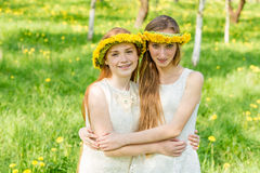 Οι φίλες στέκονται με τα στεφάνια των πικραλίδων στο hea τους Στοκ φωτογραφία με δικαίωμα ελεύθερης χρήσης