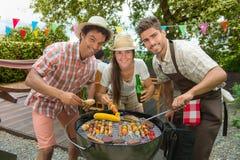 Οι φίλοι ευτυχείς κατά τη διάρκεια μιας σχάρας στην οικογένεια καλλιεργούν BBQ Στοκ φωτογραφία με δικαίωμα ελεύθερης χρήσης