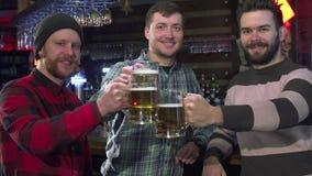 Οι φίλοι θέτουν με τα ποτήρια της μπύρας στο μπαρ φιλμ μικρού μήκους