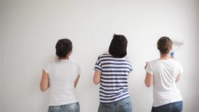 Οι φίλοι κάνουν τις επισκευές στο σπίτι Τα αστεία κορίτσια χορεύουν και χρωματίζουν τους τοίχους στο επίπεδο