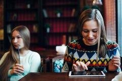 Οι φίλοι κοριτσιών επικοινωνούν σε έναν καφέ Στοκ Εικόνες