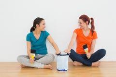 Οι φίλοι με τις βούρτσες και το χρώμα μπορούν συνεδρίαση σε ένα καινούργιο σπίτι Στοκ εικόνα με δικαίωμα ελεύθερης χρήσης