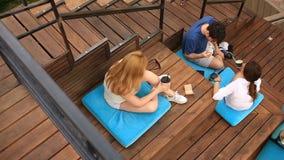 Οι φίλοι πίνουν τον καφέ και τη συνομιλία σε έναν άτυπο υπαίθριο καφέ Γρήγορο φαγητό απόθεμα βίντεο