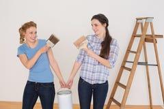 Οι φίλοι που κρατούν το χρώμα βουρτσίζουν και μπορούν σε ένα καινούργιο σπίτι Στοκ φωτογραφία με δικαίωμα ελεύθερης χρήσης
