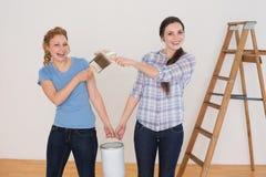 Οι φίλοι που κρατούν το χρώμα βουρτσίζουν και μπορούν σε ένα καινούργιο σπίτι Στοκ εικόνες με δικαίωμα ελεύθερης χρήσης