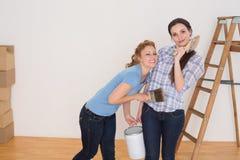 Οι φίλοι που κρατούν το χρώμα βουρτσίζουν και μπορούν σε ένα καινούργιο σπίτι Στοκ Εικόνα