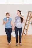 Οι φίλοι που κρατούν το χρώμα βουρτσίζουν και μπορούν σε ένα καινούργιο σπίτι Στοκ Εικόνες