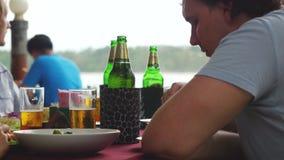 Οι φίλοι που μιλούν πίνουν την μπύρα και την κατανάλωση σε ένα εστιατόριο κοντά στην ακτή 3840x2160 φιλμ μικρού μήκους