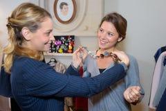 Οι φίλοι που προσπαθούν στα περιδέραια ντύνουν από δεύτερο χέρι την πώληση Στοκ φωτογραφία με δικαίωμα ελεύθερης χρήσης