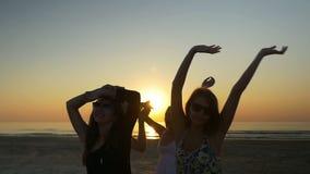 Οι φίλοι που χορεύουν ευτυχώς και που κυματίζουν τους παραδίδουν τον αέρα στην παραλία στην ανατολή απόθεμα βίντεο