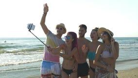 Οι φίλοι στην παραλία που έχει τη λήψη των φωτογραφιών με το selfie κολλούν απόθεμα βίντεο