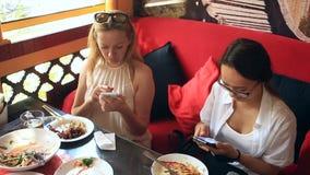 Οι φίλοι τρώνε τα κινεζικά τρόφιμα σε ένα κινεζικό εστιατόριο Κορίτσια με τα τηλέφωνα σε ένα εστιατόριο απόθεμα βίντεο