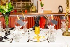 Οι φιλοξενούμενοι γενεθλίων παρουσιάζουν τη ρύθμιση με τα φρέσκα λουλούδια στο μαύρο και χρυσό ύφος, εσωτερικό Στοκ Εικόνες