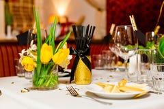 Οι φιλοξενούμενοι γενεθλίων παρουσιάζουν τη ρύθμιση με τα φρέσκα λουλούδια στο μαύρο και χρυσό ύφος, εσωτερικό Στοκ Εικόνα
