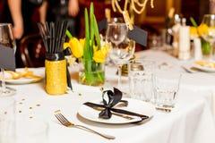 Οι φιλοξενούμενοι γενεθλίων παρουσιάζουν τη ρύθμιση με τα φρέσκα λουλούδια στο μαύρο και χρυσό ύφος, εσωτερικό Στοκ εικόνα με δικαίωμα ελεύθερης χρήσης