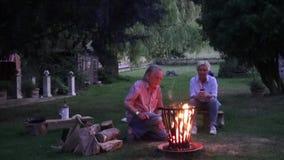 Οι φλόγες στο καλάθι πυρκαγιάς της πυράς προσκόπων θερμαίνουν το ελκυστικό ζεύγος φιλμ μικρού μήκους