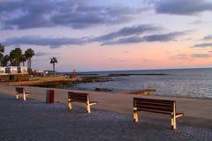 Οι φοίνικες πάγκων περιπάτων θάλασσας καλύπτουν την ήρεμη ηρεμία του ηλιοβασιλέματος στοκ φωτογραφία με δικαίωμα ελεύθερης χρήσης