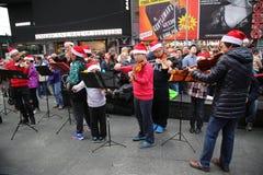 Οι φορείς βιολιών εκτελούν τα τραγούδια Χριστουγέννων τακτοποιούν κατά περιόδους στη ημέρα των Χριστουγέννων στο Μανχάταν Στοκ φωτογραφία με δικαίωμα ελεύθερης χρήσης