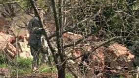 Οι φορείς του airsoft περπατούν κοντά στο τουβλότοιχο απόθεμα βίντεο