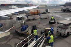 Οι φορτωτές στον αερολιμένα ξεφορτώνουν τις αποσκευές από τα αεροσκάφη Στοκ Εικόνες