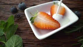 Οι φράουλες που βρίσκονται σε μια άσπρη πιατέλα ποτίζονται με το φρέσκο γιαούρτι r απόθεμα βίντεο