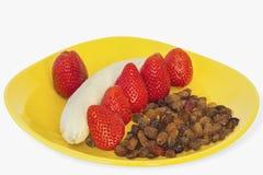 Οι φράουλες ξεραίνουν τα σταφύλια και την μπανάνα στο κίτρινο πιάτο Στοκ εικόνα με δικαίωμα ελεύθερης χρήσης