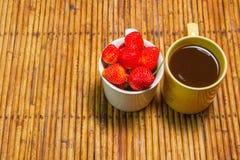 Οι φράουλες στο φλυτζάνι και τον καφέ, υπόβαθρο ινδικού καλάμου, επιλέγουν την εστίαση στοκ εικόνα