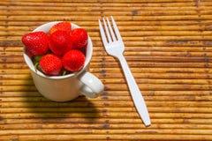 Οι φράουλες στο φλυτζάνι, υπόβαθρο ινδικού καλάμου, επιλέγουν την εστίαση στο strawberri Στοκ εικόνες με δικαίωμα ελεύθερης χρήσης