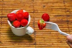 Οι φράουλες στο φλυτζάνι, υπόβαθρο ινδικού καλάμου, επιλέγουν την εστίαση στο strawberri Στοκ Φωτογραφίες