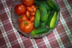 Οι φρέσκα ντομάτες και τα αγγούρια σε ένα κύπελλο γυαλιού σε ένα καρό παρουσιάζουν το ύφασμα στοκ εικόνα