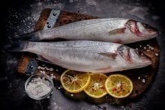 Οι φρέσκες ακατέργαστες πέρκες θάλασσας αλιεύουν με το άλας και το λεμόνι στον ξύλινο τέμνοντα πίνακα Στοκ φωτογραφία με δικαίωμα ελεύθερης χρήσης