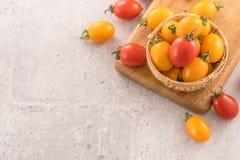 Οι φρέσκες κίτρινες και κόκκινες ντομάτες κερασιών σε ένα καλάθι σε έναν πίνακα τσιμέντου, κλείνουν επάνω, αντιγράφουν τη διαστημ στοκ εικόνα