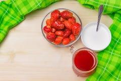 Οι φρέσκες φράουλες σε ένα γυαλί κυλούν, φράουλα mors, κρέμα σε ένα κεραμικό κύπελλο, πράσινη πετσέτα σε ένα ξύλινο υπόβαθρο Στοκ Εικόνες